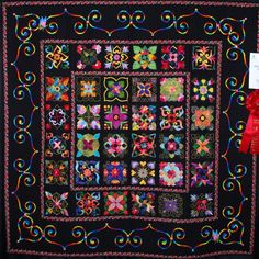 Affairs of the Heart - Miriam Reed, Grandview, CO - This design from Affairs of the Heart by Aie Rossmann, consists of 36 applique blovks on a black background.  Hearts in the border are reverse appliqued.