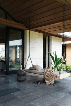decoracion jardin, terraza con suelo de baldosas, cama colgante con cobija, mesa pequeña, planta