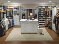 Seamless Transition - A large doorway allows this closet by ClosetMaid to flow seamlessly off the master bedroom. The door also defines the his-and-hers zones of the closet, which are equipped with shelving, rods, a hutch for him and shoe storage for her. A double center island with a bench unites the space and adds extra storage space.