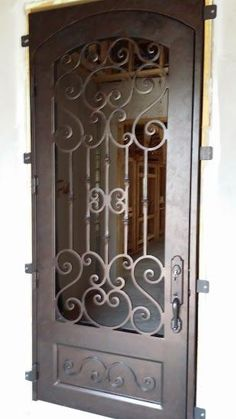 Building a new house? Consider purchasing a wrought iron door for your entryway like this showstopping number. home remodel. Iron Front Door, Front Doors, Single Door Design, Entry Doors, Entryway, Steel Security Doors, Wrought Iron Doors, Metal Clock, Iron Decor
