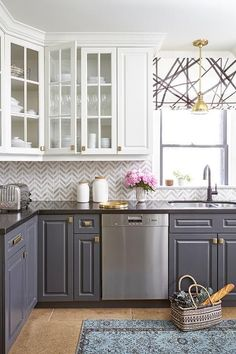 Stunning kitchen features white upper cabinets and gray lower cabinets adorned with brass hardware paired with black quartz countertops and white and gray marble chevron backsplash tiles.