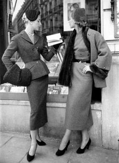 Red suit with black astrakhan hat and muff (left), and brown skirt with nutria-lined coat (right), both suits by Pierre Balmain, French, autumn/winter 1953.