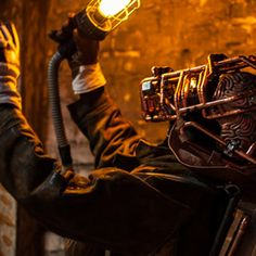 With glowing copper eyes, steam filled facial pipes and a miner's lamp, this unique roaming artist's costume is fashioned from real leather, copper and wood. Steampunk Robots, Walkabout, Real Leather, Party Ideas, Pipes, Lamps, Facial, Copper, Costume