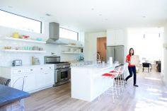 Jeanine & Jack's Zesty White Kitchen - Shelves on walls under high windows flank the stove hood.  Sink in island.