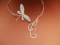 """Dragonfly Tales Torc/ Neckpiece  $179.99    With swirling elements reminiscent of wind and water, this dragonfly neckpiece flutters gracefully and softly around your neck. It is hand made in solid Sterling Silver, with the wings featuring plique-a-jour translucent resin enamel. All you need to add is your own fairy tale! Or in this case, a """"dragonfly tale""""!"""