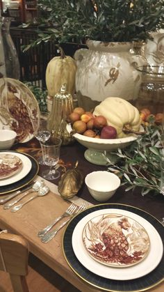 Thanksgiving table with pumpkin and turkey decor and plates.