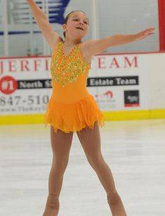 Sk8 Gr8 Designs.Custom Competition Figure Skating Dress. Gold venise lace appliques on an orange custom figure skating dress. www.sk8gr8designs.com