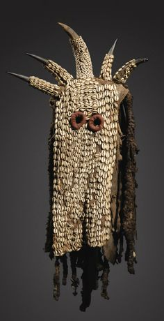 """Africa   A """"Yegue"""" mask from the Ku'ngang society of the Bamileke people of Cameroon   Natural fiber hood covered in cowrie shells, topped with horns and long braids of hair at the back."""