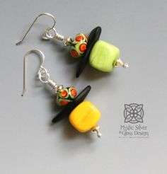 "Flamework glass lantern earrings. Casual, bright colors -Yellow & Lime. The square bottom bead is hollow, so the earrings are lightweight and comfortably wearable all day long. Colored glass beads are crafted in our studio from a molten state in a 1200 degree torch flame. Earrings measure approximately 1 1/2 "" long and 1/2"" wide. Sterling silver wire & beads.One-of-a-kind.Free shipping in continental USA. Additional shipping charges for International deliveries TBD. Customers responsible Glass Design, Colored Glass, Bright Colors, Lanterns, Glass Beads, Lime, Free Shipping, Sterling Silver, Studio"