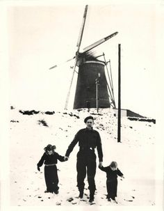 1944- Canadian soldier walks with two small Dutch children in front of windmill near Wijchen, Holland.