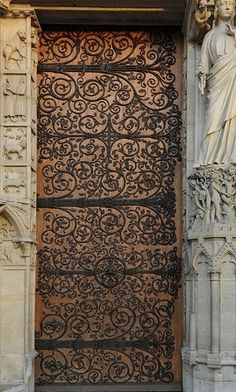 Wooden door with elaborate wrought iron hinges surrounded by carved stone: at the sept in Casterly Rock (Notre Dame de Paris)