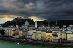 """Salzburg, Österreich ~ oh, how many times I've driven on the street that runs in front of these buildings along the Salzach River. Untersberg (background, right) in the dark clouds and fortress Hohensalzburg on the hilltop. Miss """"my"""" beloved city!"""