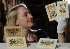 Assistant Curator Helen Thornton with silk Christmas cards which were sent during the First World War. They are from a large collection at York Castle Museum.