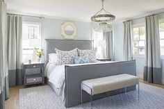 Well designed gray bedroom is furnished with a gray upholstered bed dressed in white and gray bedding topped with gray and blue pillows lit by a beaded chandelier.