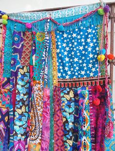 22 1/2 X 48  Made from scratch...and Eye Catching!  Fabric strips hang loose to blow in the breeze! Embellished with fringe, pompoms, bells that will jingle lightly as it moves. Assembled from a variety of vintage textiles, scarves, upcycled clothing and vibrant ethnic fabrics in a variety of textures and designs. 3 metal grommets at top Sturdy enough to hang out on the porch, but light weight enough to hang with push-pins so as not to damage the wall. Can be hung behind a bed,in a…