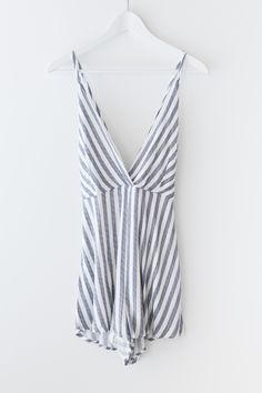 Navy blue striped romper with a V neckline and criss-cross straps in the back. Elasticated and stretchy waistband. Made with lightweight non-stretch woven material, romper is fully lined. Hidden back