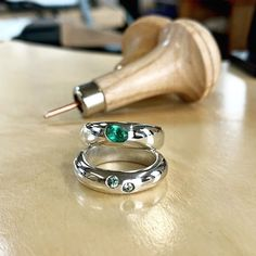 Lisa carved these two rings from wax. The bottom ring was cast in silver and then Gypsy set with two green sapphires. The top ring was set with a oval synthetic tourmaline into the wax and this was then cast into place. Two different types of setting, both with stunning results.