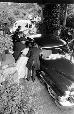 Elevated view as well-wishers gather around the car that carried newly wed future US President John F Kennedy and Jacqueline Kennedy to their wedding reception, Newport, Rhode Island, September 12, 1953.