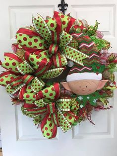 This large Christmas wreath featuring 3 handmade bows, tons of ribbon tails and a cute little elf will look amazing on your door!