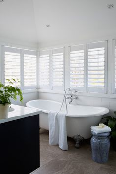 Queenslander style bathroom .White shutters ,claw foot bath , perfect white .
