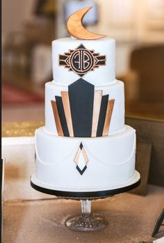 Art Deco Great Gatsby Inspired Wedding Cake in black and gold, complete with sugar Art Deco fan design and hand-piped personalised Wedding Monogram