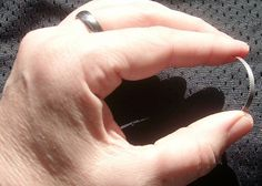 Titanium Escape Ring. A simple but elegant-looking ring made of titanium, cut from solid barstock and polished to a mirror finish.  Contains a saw and handcuff shim pick combination tool which is completely hidden from view when worn.  The shim can be used to open single-locked handcuffs, while the saw can cut zip-ties, disposable handcuffs, duct tape, rope, and other non-metallic materials.