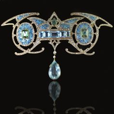 Magnificent Art Nouveau Brooch in 18ct yellow gold, with a central aquamarine panel suspending a large aquamarine drop inbetween two green tourmalines within enamelled oval forms and diamond detailing Georges Fouquet, Paris circa 1901| JV