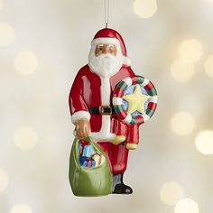 "Shop Around the World Philippines Santa Ornament.  Dressed in a traditional red suit with white fur trim and matching hat, our Filipino Santa ornament carries a ""parol"" or Christmas lantern along with his big bag of gifts."
