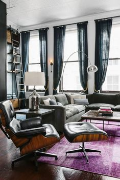 Moody living space with large windows, a silver floor lamp, a gray sectional, and Eames lounge chair, and a ladder New Yorker Loft, Loft Style Apartments, Loft Stil, Style Loft, Lounge Chair, Chaise Lounges, Contemporary Floor Lamps, Living Spaces, Living Room