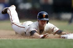 San Francisco Giants Buster Posey slides safely into third base after a wild pitch by the Philadelphia Phillies during the 10th inning of a baseball game, Wednesday, May 8, 2013, in San Francisco. San Francisco won 4-3. (AP Photo/Marcio Jose Sanchez)
