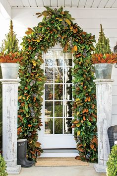 Attention-Grabbing Archway - These Porches Got a Merry Makeover for the Holidays - Southernliving. This archway combines a few of the South's quintessential Christmas greenery, like pinecones and magnolia leaves, for a show-stopping entryway. Country Christmas Decorations, Christmas Greenery, Farmhouse Christmas Decor, Holiday Decorating, Christmas Trimmings, Christmas Arrangements, Christmas Centerpieces, Decorating Ideas, Outdoor Christmas Garland