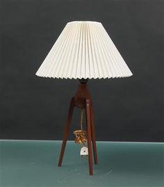 Bordlampe på trebenet stel af teak. Monteret med hvid Le Klint skærm med enkelte trykmærker. 1960'erne. H. med skærm. 59 cm
