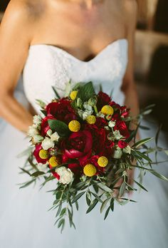 Brides.com: . A winter wedding bouquet comprised of burgundy peonies, greenery, and craspedias created by Nerine Arte Floral.