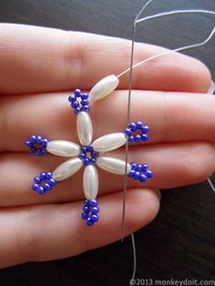 String an oval bead onto the thread and push the needle down through one seed bead from the neighbouring 'arm' of the snowflake