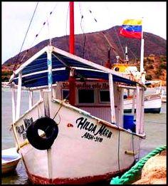 Barcos de pesca en el Muelle de la Bahía de Juan Griego y al fondo el Fortín de La Galera. Isla de Margarita. Estado Nueva Esparta.Venezuela