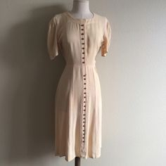 """Vintage 20s Cream Textured Silk Puff Sleeve Dress True late 1920's vintage creamy off white textured silk dress. Cute tiny Brown Bakelite button accents down the front. Hidden metal snaps closure. It is in excellent vintage condition for its age. There were some repairs done in the underarm I redid them & can't be seen when worn. No other holes or stains. Measurements are 40""""BUST// 32""""WAIST// 42"""" long top of shoulder to end. Vintage Dresses"""
