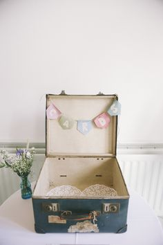 Use suitcases as containers for the post-ceremony petals, photo booth props, flowers, wedding programs and favors.