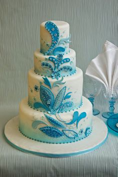 Large white cake with turquoise blue & light blue paisley prints up each layer, very pretty!