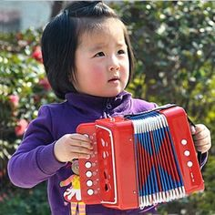 Cute little girl playing accordion.