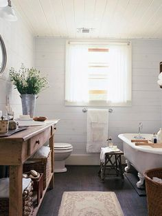 General coloring. Whiteish plank walls, natural wood vanity, darker floors, white clawfoot tub.