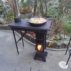 a rocket stove with attachments, first the stove like table with the chimney, but the fabricator Mr. Sugiura, has a square or an arch type oven that go on top the rocket stove replacing that stove top. Good idea if one wants to custom made this kind