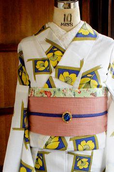 白地に綺麗なブルーと黄色で、エルメスのスカーフのデザインを思わせるようなモダンでスタイリッシュな中に物語を感じるモチーフが染め出されたレトロ浴衣です。
