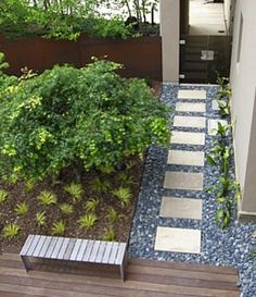 Set square paving stones into a bed of darker-colored loose stones to create a more modern walkway.