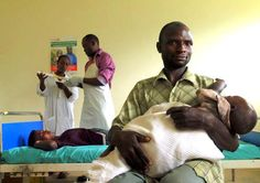 While her husband holds their youngest child, Twesigye Christente waits to receive a long-acting contraceptive at the Kinaaba Health Center II. Photo: Omar Gharzeddine