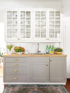 Stephanie Kraus Design White glass front upper cabinets mount over dove gray lowers accented by polished nickel cup pulls and knobs. Kitchen Decor, New Kitchen, Glass Upper Cabinets, Small Kitchen, Home Kitchens, Kitchen Nook, New Kitchen Cabinets, Kitchen Design, Kitchen Renovation