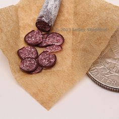 Thin slices and a section of an artisan style salami, made from polymer clay in 1:12 dollhouse scale.