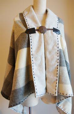 ウール100%の生地を2枚合わせで作りました。表地はグレーと濃いグレーと白のチェック、裏は薄いグレーで裏もウールです。とても暖かいです。縁取りもウールの毛糸(100%)紺色で手縫いしました。ボタンはココナッツ、コードと留めはレザーでナチュラルな仕上がりです。サイズ横147cm 縦68cmココナッツボタンの直径 5cm