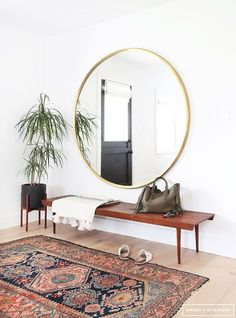 Midcentury modern meets bohemian entryway with a slatted bench, vintage Persian rug and oversized gold round mirror.