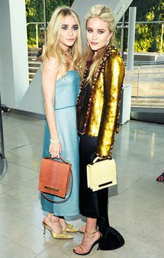 Ashley Olsen in a light blue The Row dress and Mary-Kate wearing a statement gold jacket