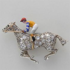 A late Victorian diamond and enamel brooch in the form of a galloping racehorse and jockey, the finely modelled horse encrusted with rose, single and old-cut diamonds, the saddle, bridle and stirrup detailed in yellow gold, the enamel jockey wearing yellow, blue and white silks, mounted in silver to a yellow gold reverse, measuring 3.5 x 2.5cm, gross weight 7.6 grams, circa 1890.